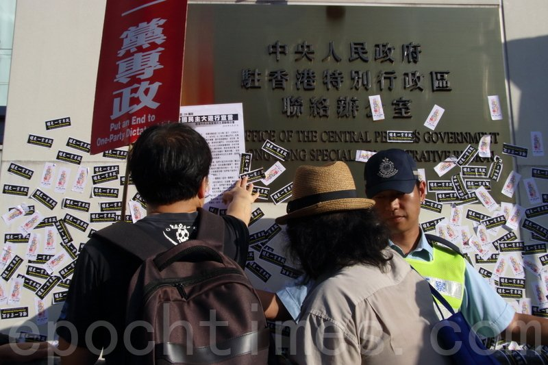 遊行隊伍下午5時許抵達終點中聯辦,遊行人士將「結束一黨專政」的貼紙及宣言貼在中聯辦外。(蔡雯文/大紀元)