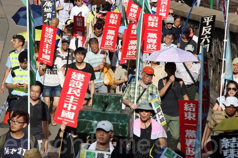 有市民手持寫有「抗威權」的海報及紙製坦克車,要求平反「六四」。(李逸/大紀元)