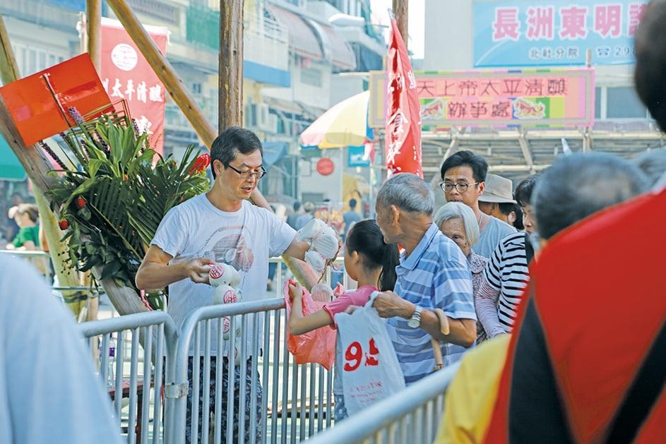 香港長洲太平清醮值理會總理鄺世來在北帝廟前廣場幫忙派平安包。(陳仲明/大紀元)