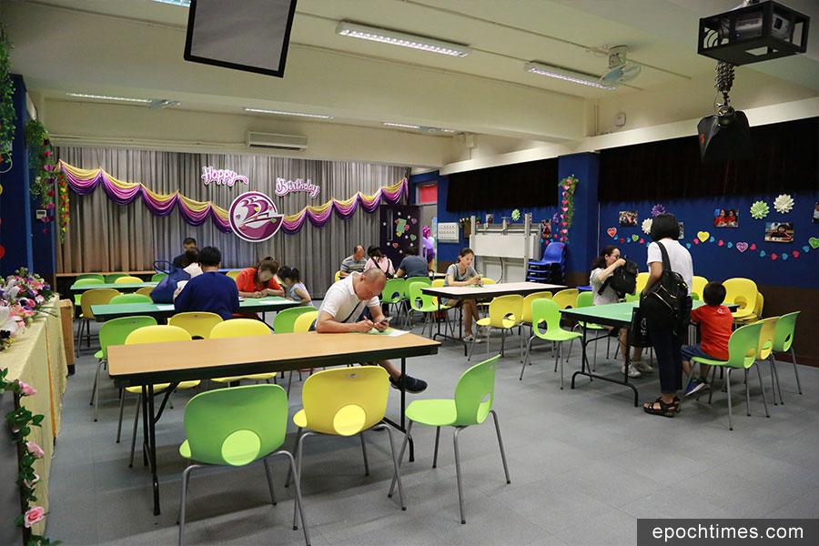 多位家長帶同子女到香海正覺蓮社佛教陳式宏學校叩門。圖為家長們正在填寫申請表中。(陳仲明/大紀元)