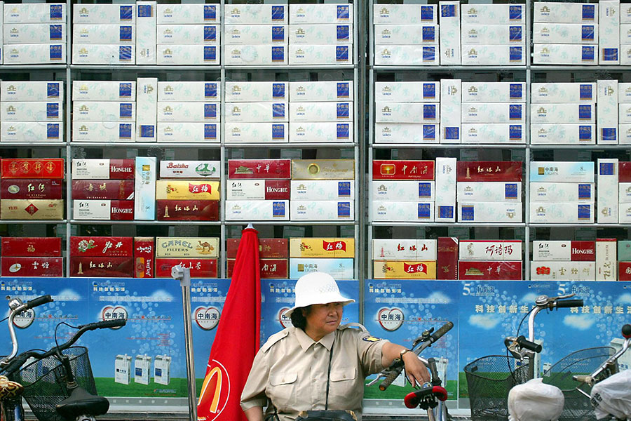 中共官方一方面壟斷煙草銷售,一方面打擊地下香煙工廠。圖為一個泊車管理員坐在一家銷售香煙的商店外面。(AFP/Getty Images)