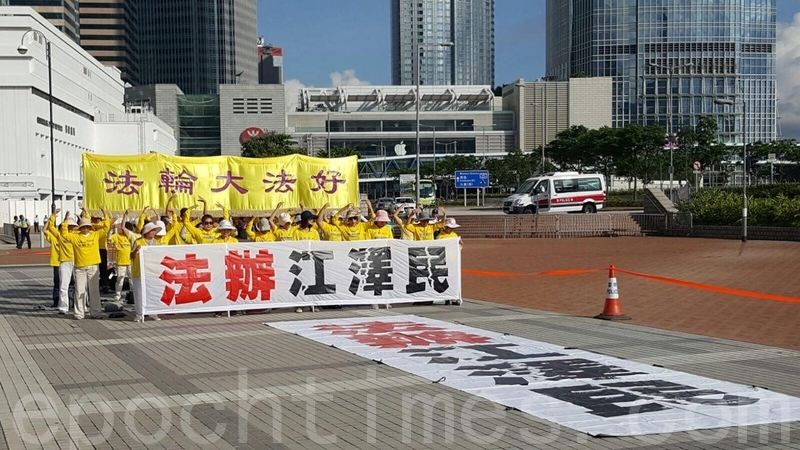 圖為香港法輪功學員,早上在愛丁堡廣場集體煉功,遙向習近平下榻的海景萬麗酒店,打出「法辦江澤民」的巨型橫幅。(林怡/大紀元)