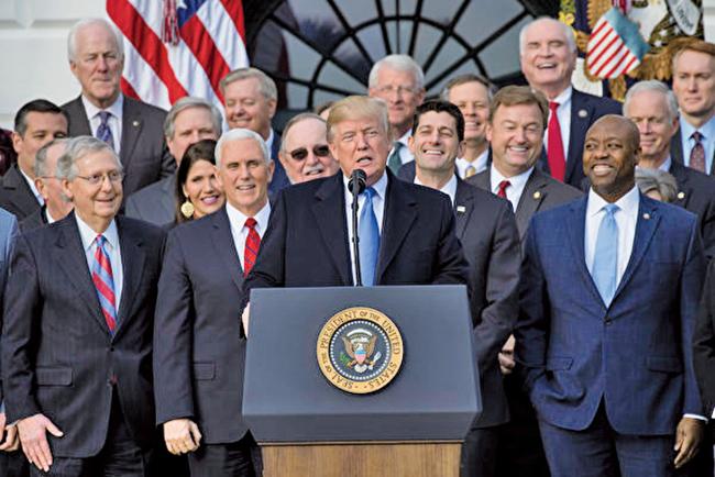 美國總統特朗普在去年12月簽署「減稅和就業法案」,目前已經使美國家庭、工人和公司受益。圖為特朗普、副總統彭斯和共和黨國會議員在白宮合影。(AFP)