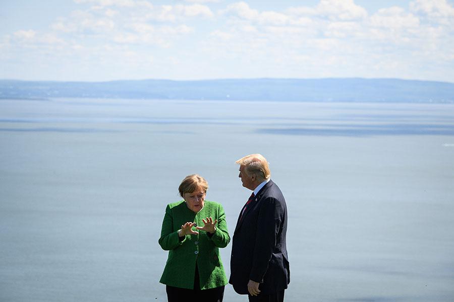 2018年6月8日,德國總理默克爾和特朗普在G7峰會合照後,密切交談。(Leon Neal/Getty Images)