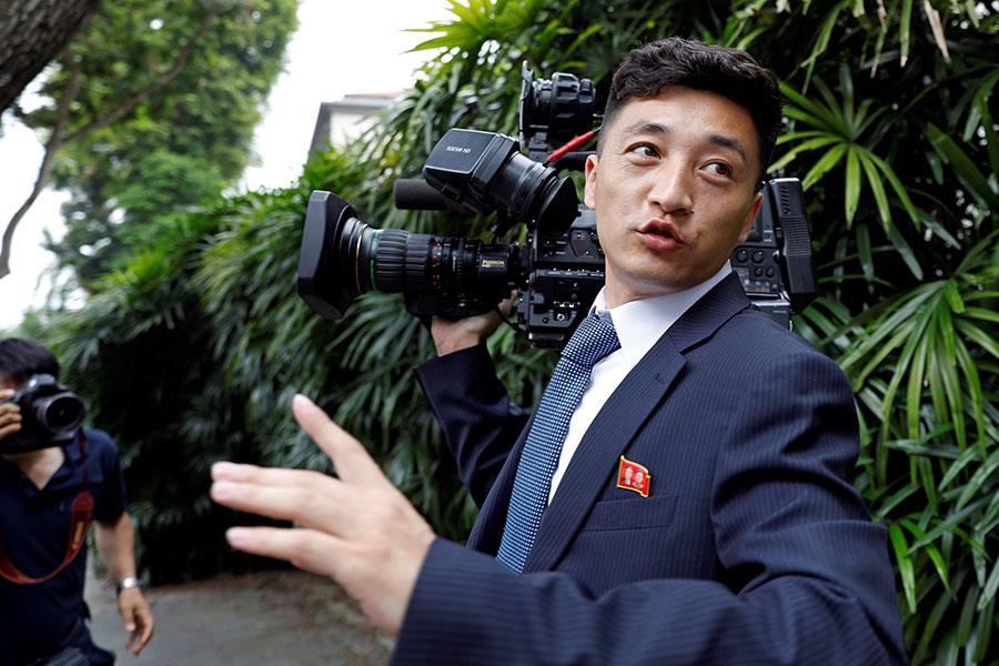 6月10日,一名北韓攝影師剛拿著攝像機走出瑞吉酒店,就招來眾多記者圍觀。(REUTERS/Tyrone Siu)
