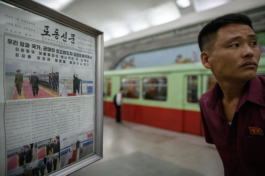 圖為12日上午,北韓當地民眾在平壤一地鐵站內觀看今日報紙的特金會消息。(ED JONES/AFP/Getty Images)