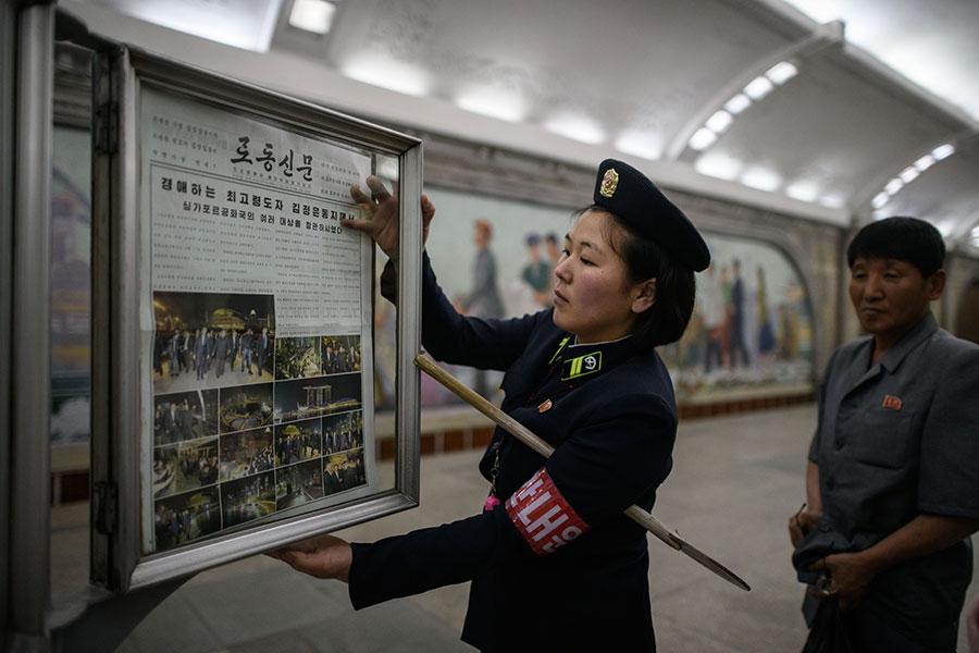 圖為12日上午,工作人員在北韓平壤一地鐵站內更換今日報紙。(ED JONES/AFP/Getty Images)