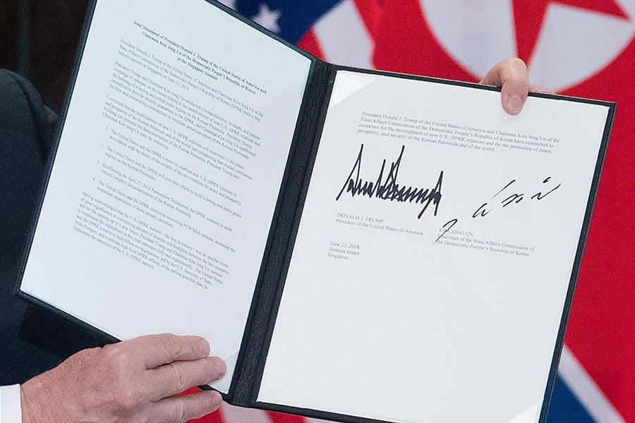 特朗普與金正恩在儀式上簽署聯合協議。(SAUL LOEB/AFP/Getty Images)