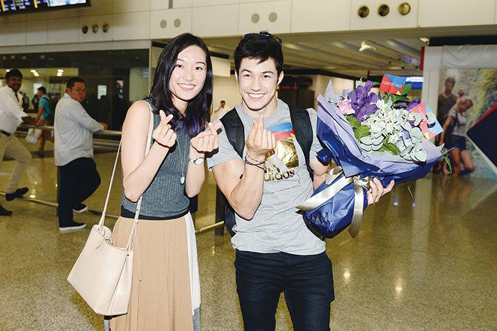 Arthur Nory步出香港機場收到粉絲送贈的鮮花,做出心心手勢開心與粉絲合照。(宋碧龍/大紀元)