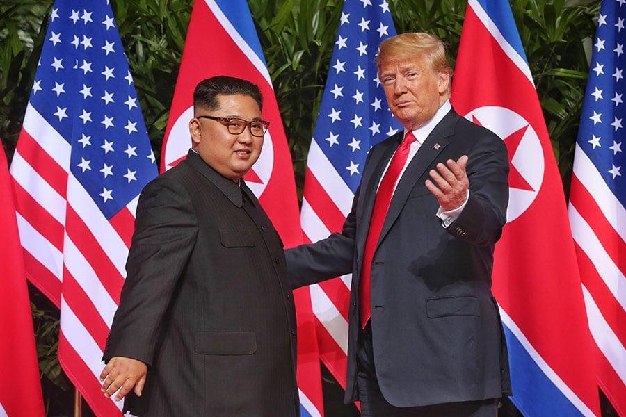 美國總統特朗普(右)12日上午9時4分於新加坡與北韓領導人金正恩互相問候,雙方隨後握手合照,實現雙方領導人73年來的破冰一握。(Kevin Lim/THE STRAITS TIMES/Handout/Getty Images)