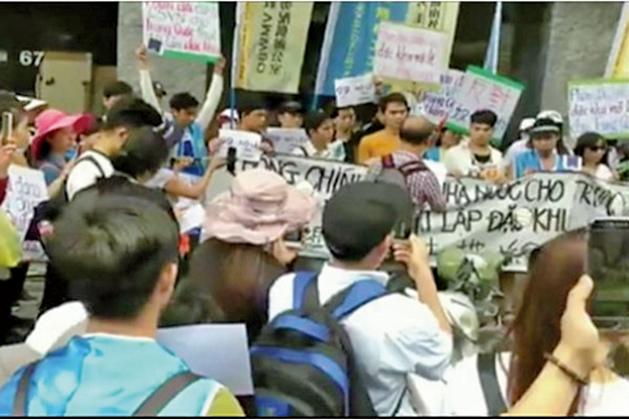 抗議者舉著反華標語牌和橫幅,其中一個橫幅上寫道「土地一天也不租給中國」。(影片截圖)