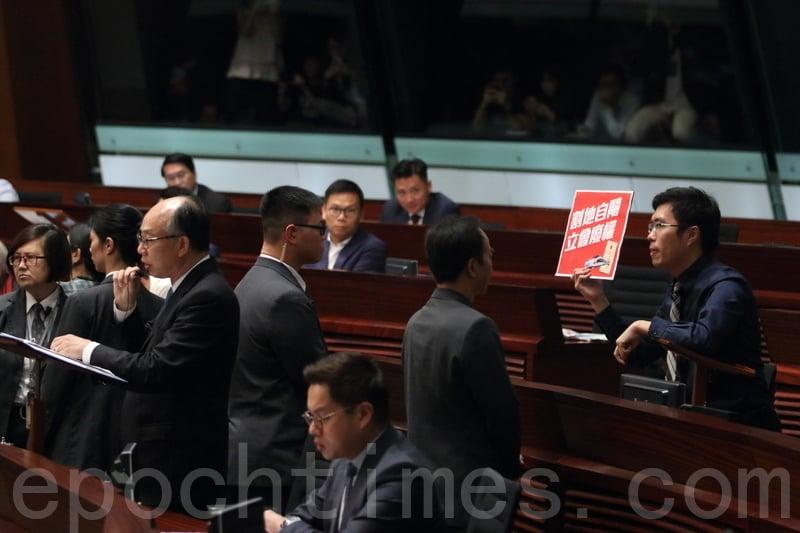 區諾軒走到陳帆後面試圖阻止他發言,被趕離會議廳。(蔡雯文/大紀元)