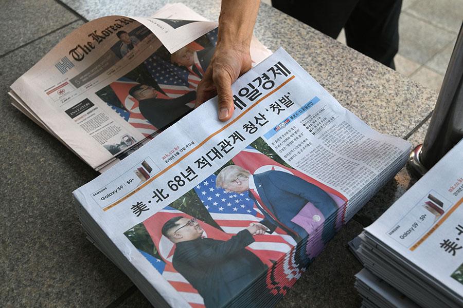 風雲變幻,誰是贏家?圖為南韓一送報工在整理關於特金會的報紙。(JUNG YEON-JE/AFP/Getty Images)