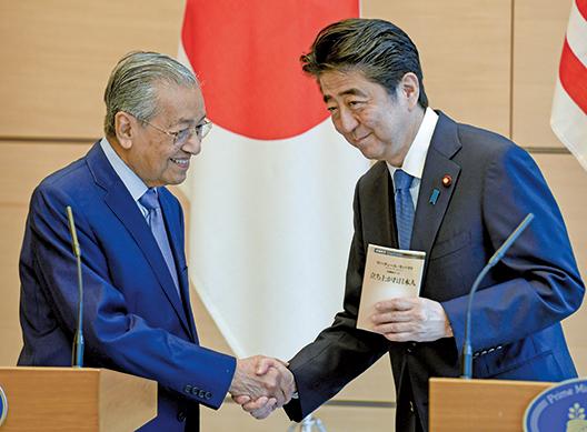6月12日,馬來西亞首相馬哈迪(左)與日本首相安倍晉三舉行雙邊會談後,在聯合新聞發佈會上握手。(AFP)