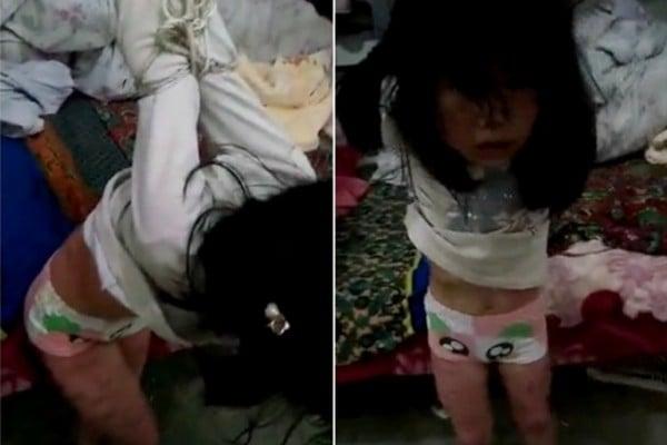 片段中,一個約4、5歲的女童,被大人反綁雙手吊在床邊,不停地被用衣架抽打。女童裸露的雙腿上佈滿了傷痕。(視像擷圖)