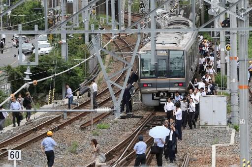 日本大阪北部6月18日上午7時58分發生6.1級地震,部份新幹線停駛。圖為乘客沿路軌徒步走回車站。(AFP)