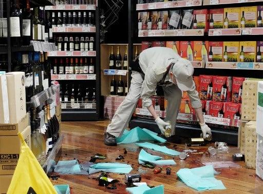 日本大阪北部6月18日上午7時58分發生6.1級地震。圖為一名店員在清理震後掉落地上破碎的瓶子。(AFP)