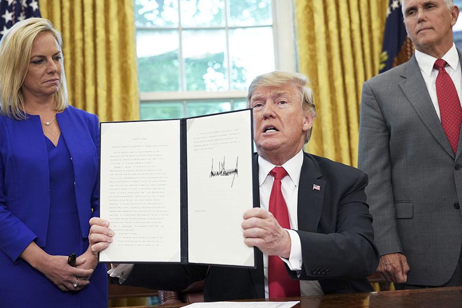 美國總統特朗普周三(6月20日)簽署了一項行政令,旨在解決美國南部邊境非法入境的家庭分離問題。行政令規定,將會允許年幼孩子和被抓父母團聚。(MANDEL NGAN/AFP/Getty Images)