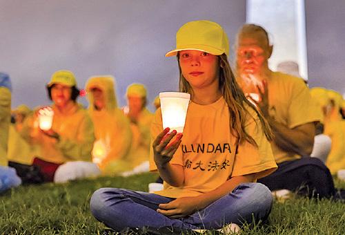 來自世界各地不同年齡層的法輪功學員燭光夜悼被中共迫害死的學員。(Mark Zou/大紀元)
