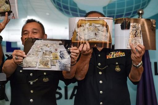 馬來西亞警方6月27日表示,警方從前首相納吉的6棟房宅裏搜出大量財物,包括現金、大批珠寶和昂貴名牌手袋,價值高達2.73億美元。圖為警方向媒體展示財物照片。(Mohd RASFAN/AFP)