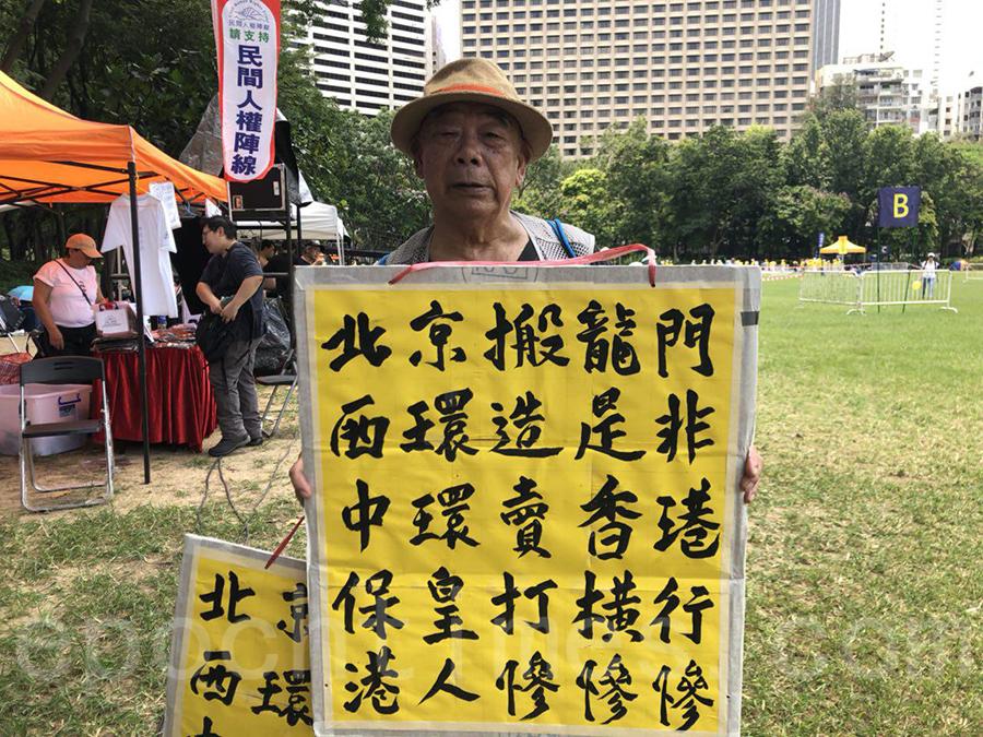 已屆94歲高齡的港人黃伯,冒著酷熱天氣參與七一大遊行,並以書法展板表達抗議中共的訴求。(梁珍/大紀元)