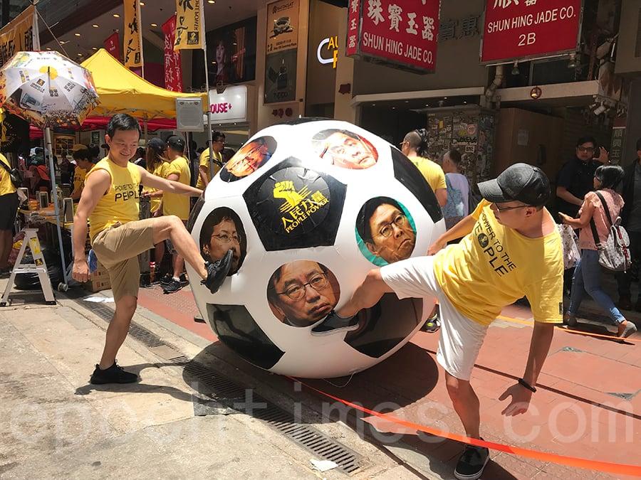 人民力量道具大足球印有代表出賣香港的林鄭月娥、梁振英、陳茂波、陳帆、梁君彥及馬時亨。(林怡/大紀元)