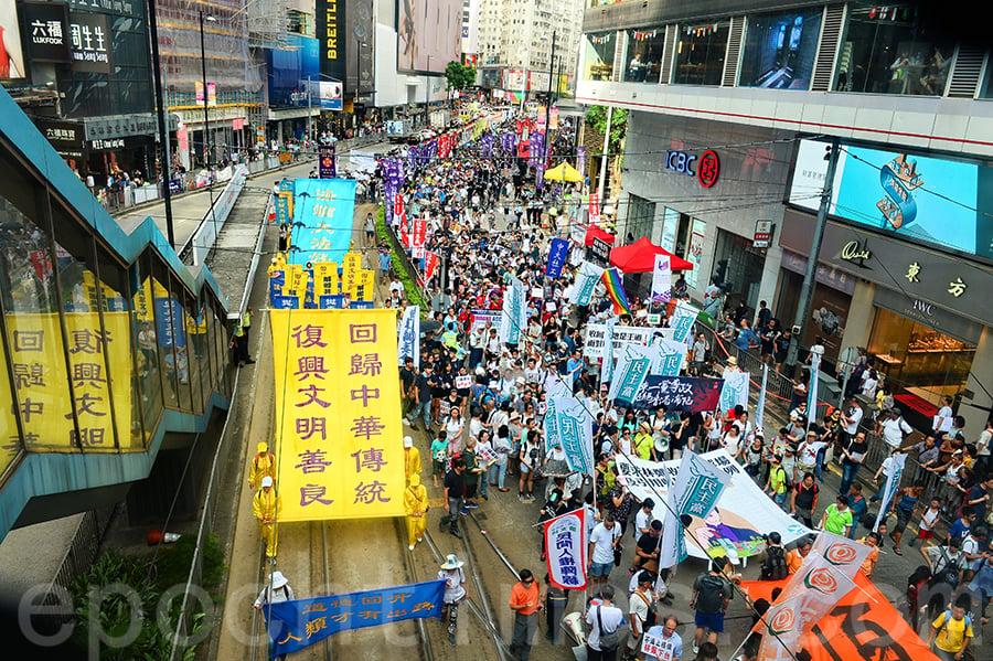 香港法輪功學員參加了民陣2018年7月1日舉行的一年一度七一大遊行,呼籲法辦迫害元兇、解體中共,整齊的隊伍和鮮明旗幡受到市民遊客的注目和讚賞。(宋碧龍/大紀元)