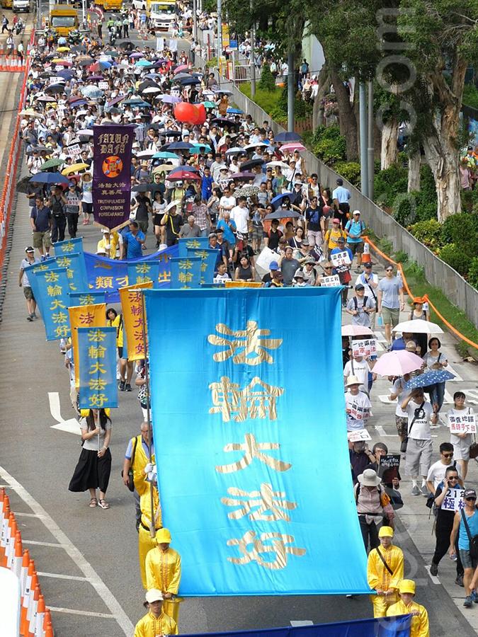 香港法輪功學員參加了民陣2018年7月1日舉行的一年一度七一大遊行,呼籲法辦迫害元兇、解體中共,整齊的隊伍和鮮明旗幡受到市民遊客的注目和讚賞。(大紀元)