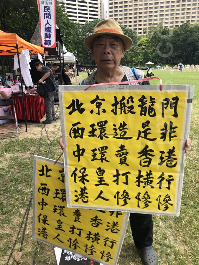 94歲港人黃伯舉著毛筆書寫的展板抗議中共和港府禍亂香港。(宋碧龍/大紀元)