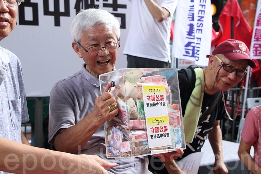 86歲高齡的天主教香港教區榮休主教陳日君樞機在七一街站為為幫助社運人士籌款打官司的「守護公義基金」籌款。(蔡雯文/大紀元)