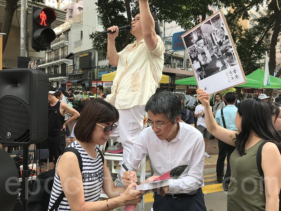 《明報》前總編輯劉進圖在七一遊行街站幫市民為新書《香港這一年》簽名。(李小朗/大紀元)