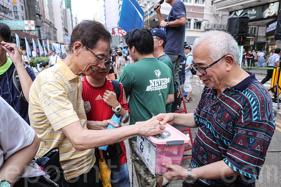 著名時事評論員程翔在七一街站為《消失的檔案》籌款,獲民主黨創黨主席李柱銘捐款支持。(余鋼/大紀元)