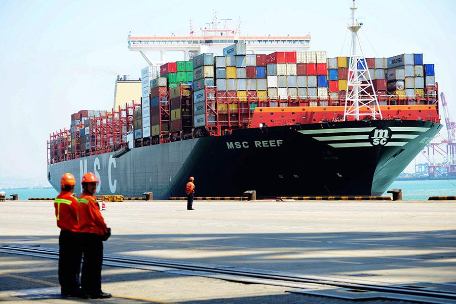 美學者表示,任何戰爭都有傷亡,但在中美貿易戰中,中共政府比美國政府更不在乎讓自己的民眾遭受苦難。圖為2017年4月13日,中國工人站在山東青島港口一艘載完貨物的貨船前。(STR/AFP/Getty Images)