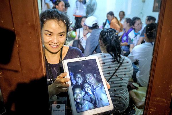 家屬展示潛水員拍攝男孩的最新相片,顯示他們露出笑容。(Getty Images)