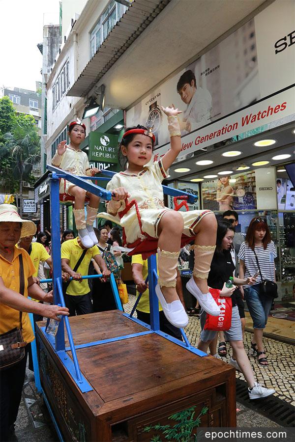 飄色巡遊的隊伍途經繁華的購物大街。(陳仲明/大紀元)