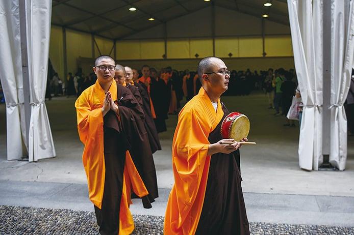 圖為2017年9月5日,135歲的上海玉佛寺大殿正式搬遷期間,佛教僧侶在寺內祈禱。(Getty Images)