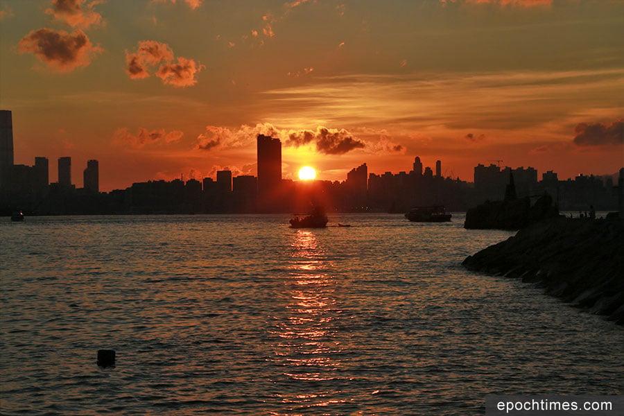 在春夏季的黃昏,從鯉魚門觀賞日落,夕陽剛好在九龍半島的天際線落下。(陳仲明/大紀元)