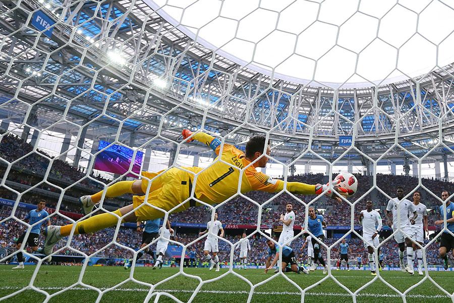 法國門將洛里斯(黃衣者)奮勇撲接烏拉圭馬田卡沙利斯的頭球攻門。(Alexander Hassenstein/Getty Images)