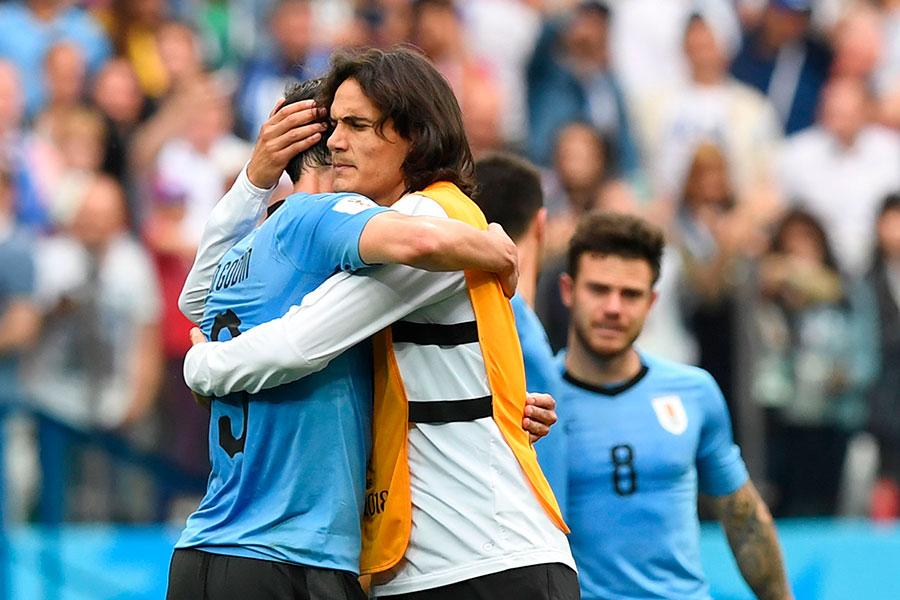 因傷缺陣的烏拉圭球員卡雲尼(右)以擁抱安慰隊友。(MARTIN BERNETTI/AFP/Getty Images)