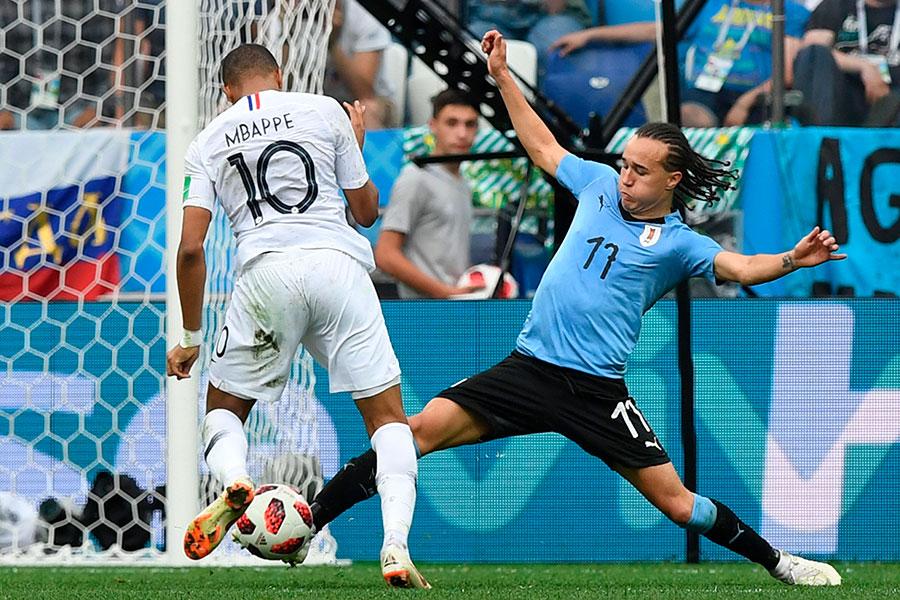 基利安麥巴比(Kylian Mbappé,左)在禁區內無人盯防下,頭球攻門射失,被烏拉圭門將迪亞高拿索特(Diego Laxalt)擋下,錯過得分良機。(MARTIN BERNETTI/AFP/Getty Images)