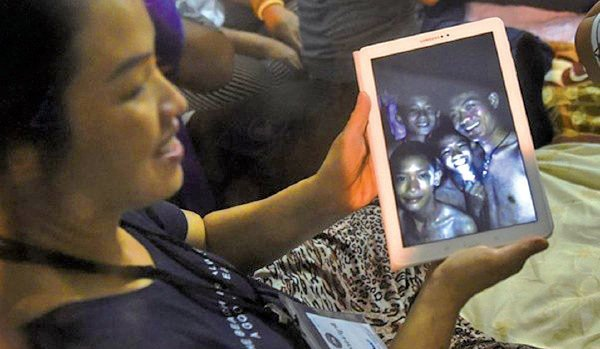 泰國12名足球隊隊員和教練被困地下洞穴10天仍奇蹟生還,教練艾卡波(右)教他們打坐成為最大功臣。圖為一名被困孩童的母親展示教練與孩童的照片。(LILLIAN SUWANRUMPHA/AFP/Getty Images)