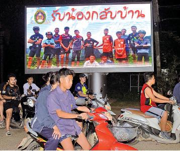 清萊府路邊一幅大告示牌上印有泰國「野豬」少年足球隊隊員和教練的照片,並寫著「兄弟們,歡迎回家」。(TANG CHHIN SOTHY/AFP/Getty Images)