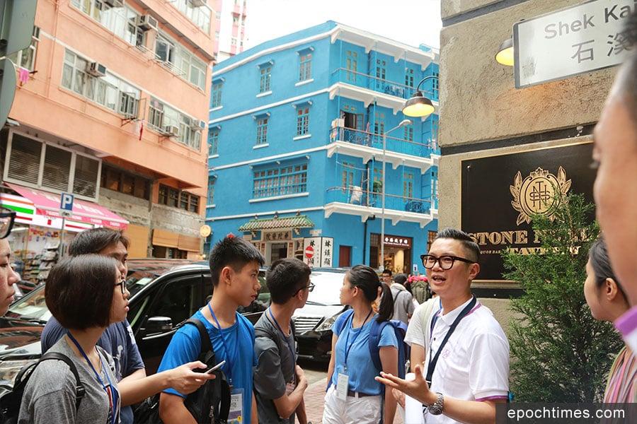 比賽籌委會主席黃健兒(右)向學生講解灣仔藍屋的發展。(陳仲明/大紀元)