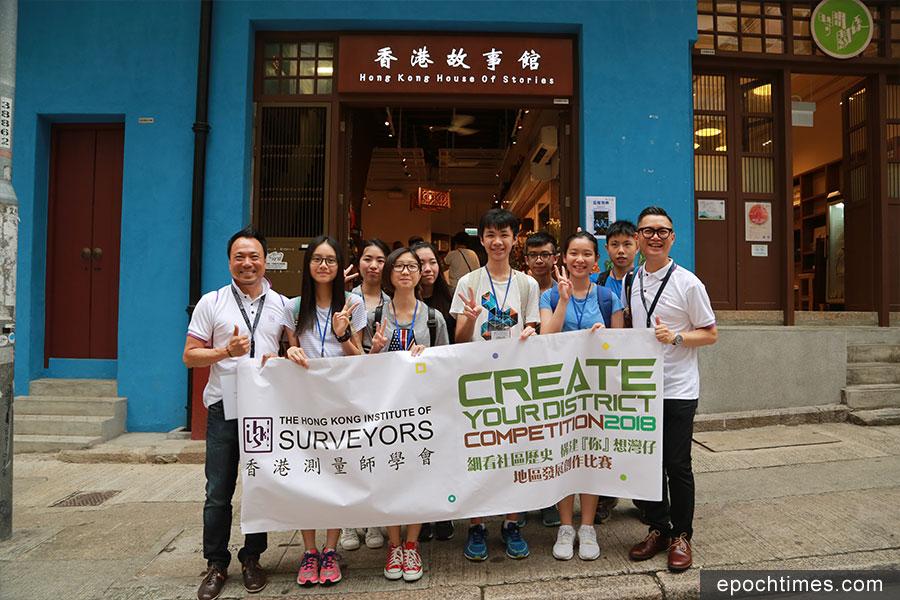香港測量師學會會長郭岳忠(左一)、副會長暨地區發展創作比賽籌委會主席黃健兒(右一)帶領學生走訪灣仔社區,認識區內建築。(陳仲明/大紀元)