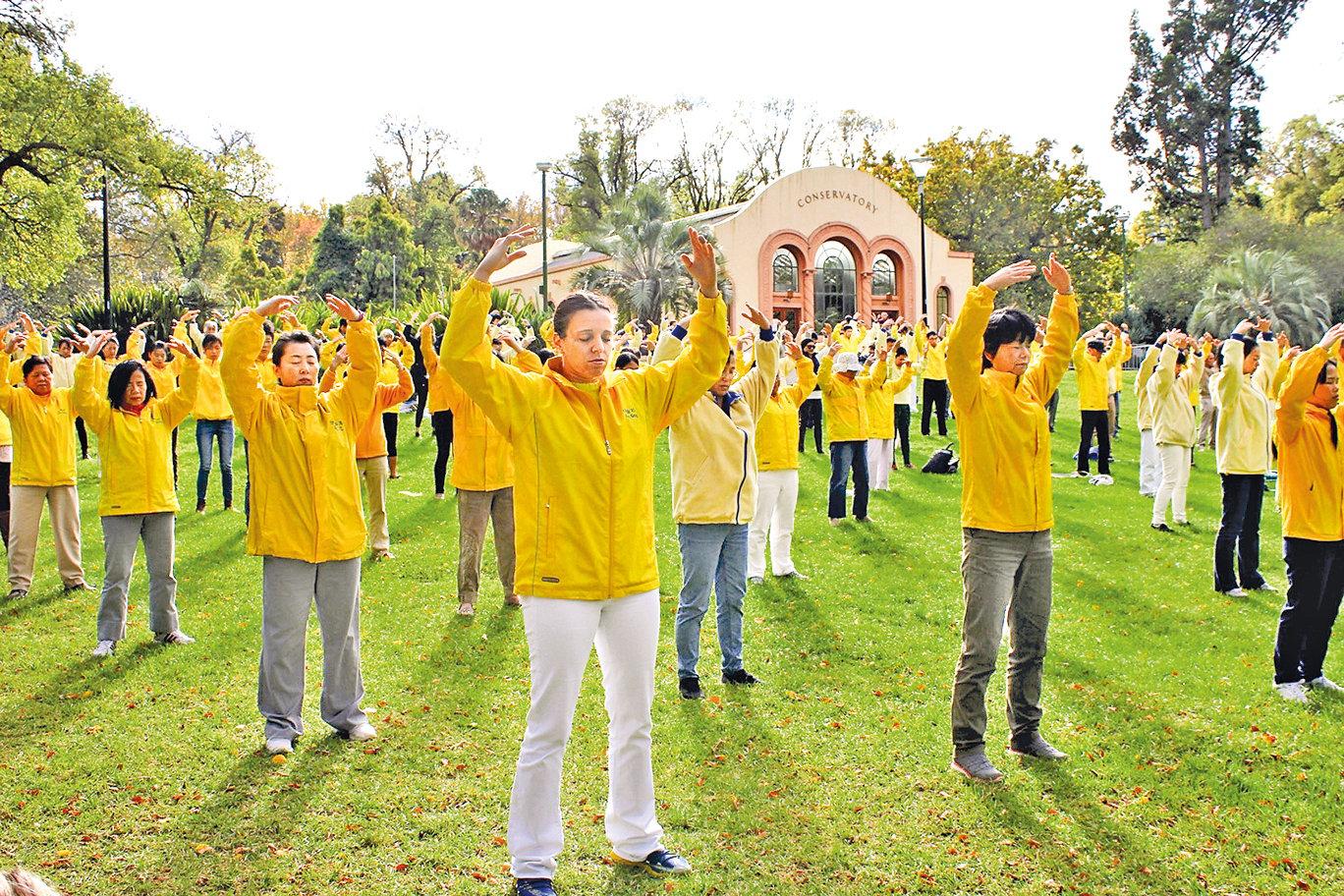 索菲亞(中)在墨爾本市中心費茨羅伊公園參加法輪功集體煉功。(明慧網)