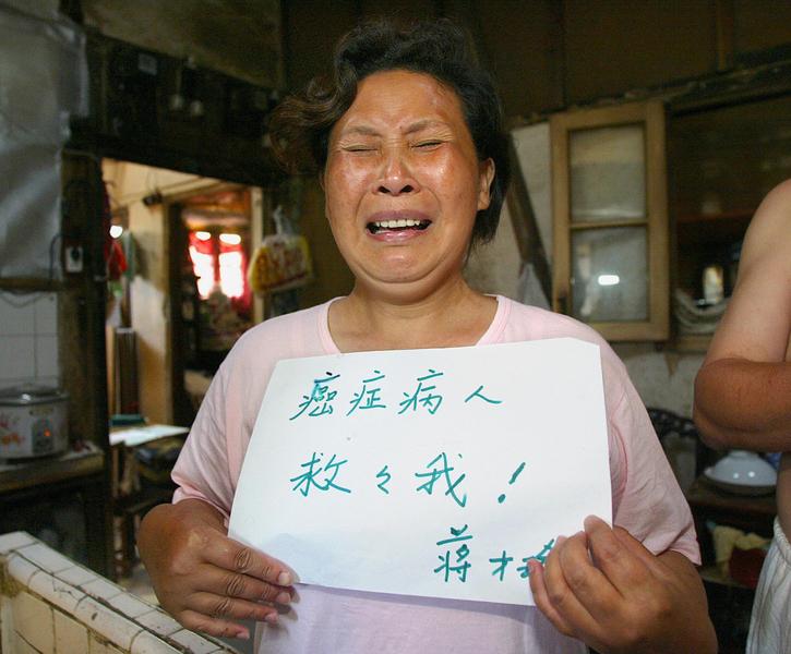 上海市疾控中心最新統計數據顯示,上海每天死於癌症約100人。圖為,一癌症病人手舉「救救我!」紙牌。(LIU JIN/AFP/Getty Images)
