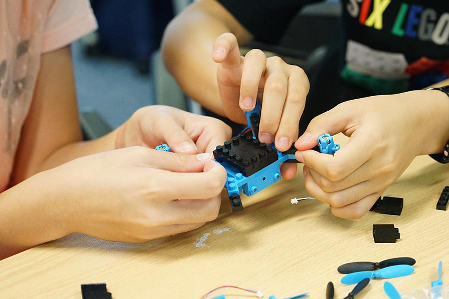 學生參與「會飛的磚塊」工作坊,合作組裝無人機。(曾蓮/大紀元)