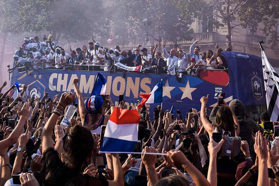 7月16日英雄凱旋,法國隊乘坐的專車受到香街兩旁民眾的熱情迎接。(LUCAS BARIOULET/AFP/Getty Images)