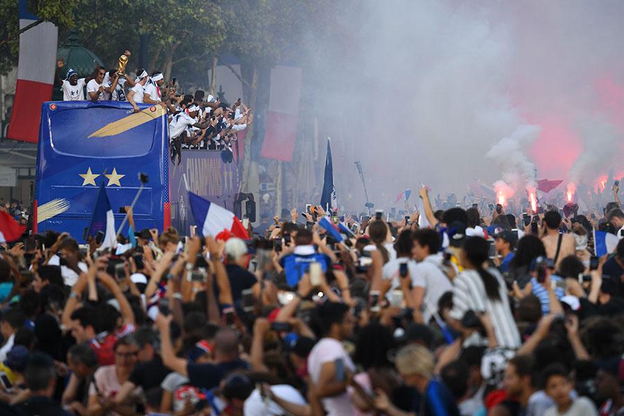 7月16日英雄凱旋,法國隊乘坐的專車受到香街兩旁民眾的熱情迎接。(ERIC FEFERBERG/AFP/Getty Images)