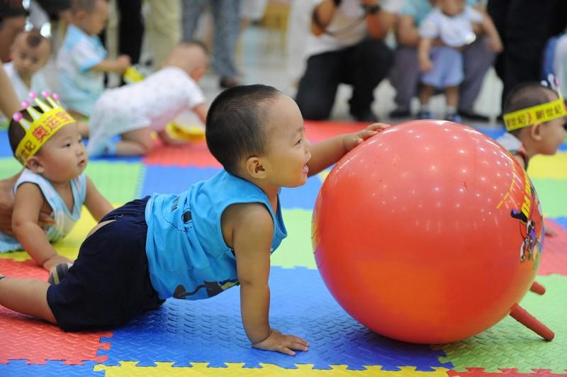 目前大陸養育一個孩子得花費一百多萬人民幣。養孩子難,成了年輕人頭疼的事。圖為2009年8月北京一家幼兒園的孩子們正在玩遊戲。(法新社)